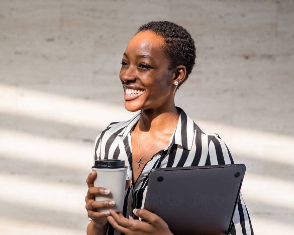 Woman holding a coffee cup and laptop.