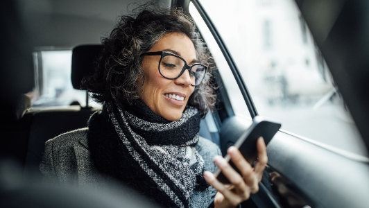 Young female looking at her phone while riding in a car
