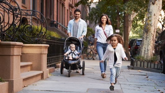 Young family walking together down urban street