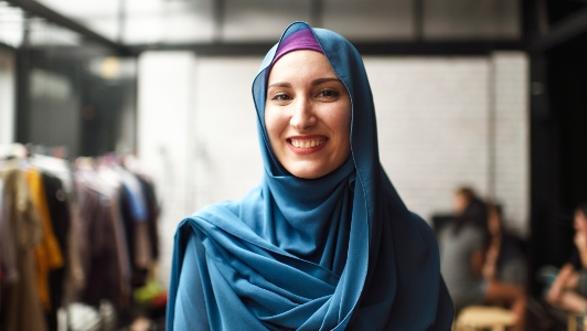 A smiling woman wearing a blue headscarf