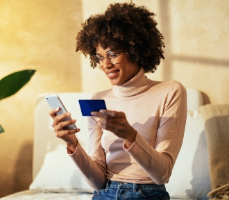 image of younger woman looking at mobile phone and holding a credit card