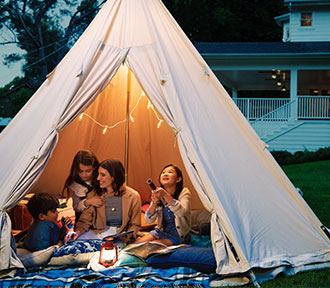 Mother with two daughters and a son, outside in a tent at night.