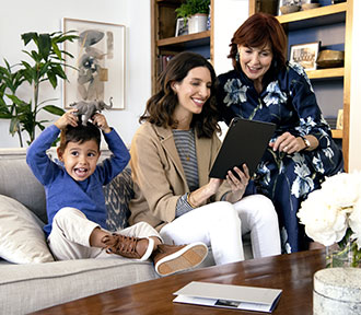 Two woman looking at a tablet, while child plays on the couch.